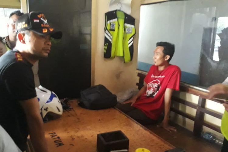 Seorang pemuda berinisial M (38), berbaju merah, diamankan oleh Satlantas Jakarta Barat di dekat Pos Lantas Cengkareng, Jakarta Barat, Rabu (23/10/2019). M diketahui membawa senjata tajam.