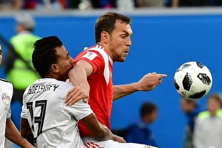 Artem Dzyuba mencoba lepas dari pengawalan Mohamed Abdel-Shafy pada pertandingan Rusia vs Mesir di St. Petersburg, 19 Juni 2018.