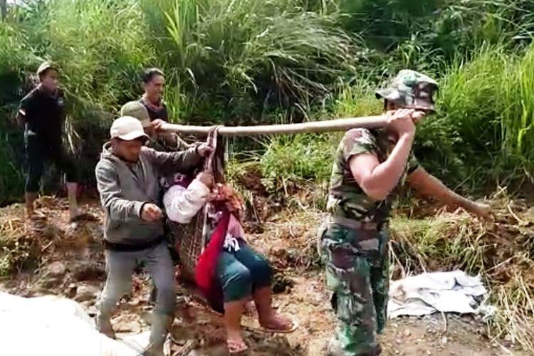 Dua anggota TNI dari Kodim 0608/Cianjur menandu seorang ibu yang baru melahirkan sejauh 2 kilometer di Desa Mekarmulya, Kecamatan Cikalongkulon, Cianjur karena kondisi jalan yang rusak.