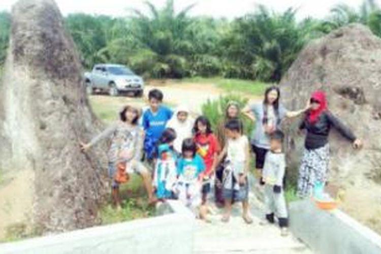 Pelancong berfoto di obyek wisata Batu Takup di Bengkulu. Saat ini Batu Takup tersebut telah dibelah di tengahnya dan dibuat jalan oleh perusahaan perkebunan.