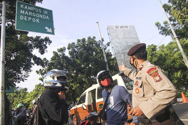 Petugas kepolisian memeriksa pengendara motor yang berpenumpang saat penerapan PSBB di perbatasan Jakarta - Depok, Depok, Jawa Barat, Rabu (15/4/2020). Pemeriksaan tersebut untuk memastikan setiap pengendara mematuhi aturan Pembatasan Sosial Berskala Besar (PSBB) yang diterapkan di Kota Depok.