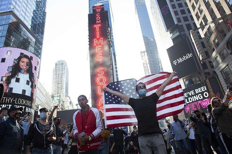 Warga merayakan kemenangan Joe Biden pada pemilihan presiden Amerika Serikat (AS) 2020 di Times Square, New York, AS, Sabtu (7/11/2020). Joe Biden dipastikan melenggang ke Gedung Putih dengan 290 suara elektoral yang diraihnya sejauh ini, mengakhiri kepemimpinan 4 tahun Donald Trump.