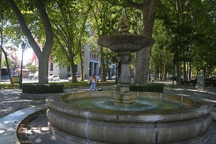 Seorang wanita berjalan di dekat air mancur di boulevard Paseo del Prado di Madrid, Spanyol, Jumat, 23 Juli 2021.