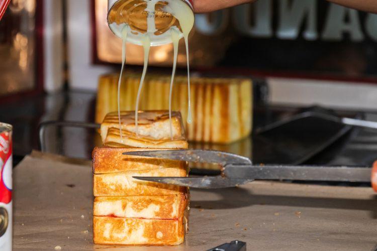 Pedagang Roti Bakar Bandung sedang menuangkan susu kental manis di roti.