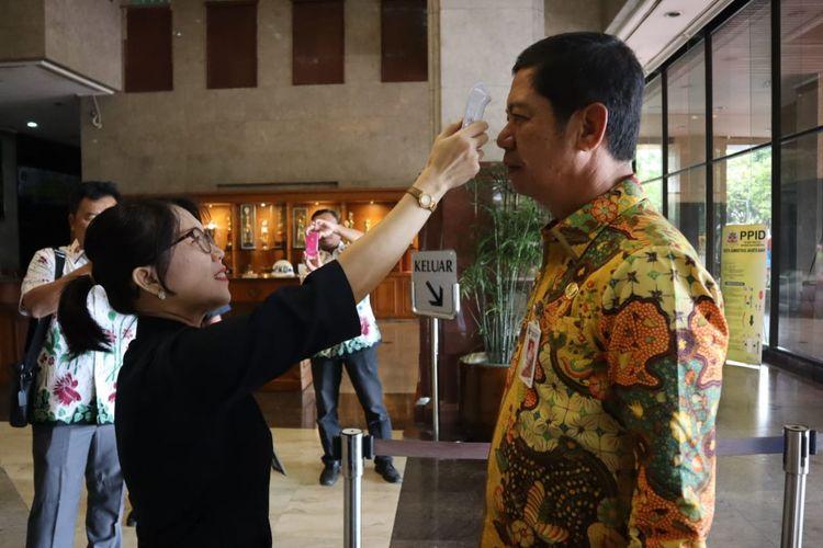 Wali Kota Jakarta Barat Rustam Effendi di cek suhu tubuhnya saat memasuki kantor Wali Kota Jakbar pada Kamis (5/3/2020)