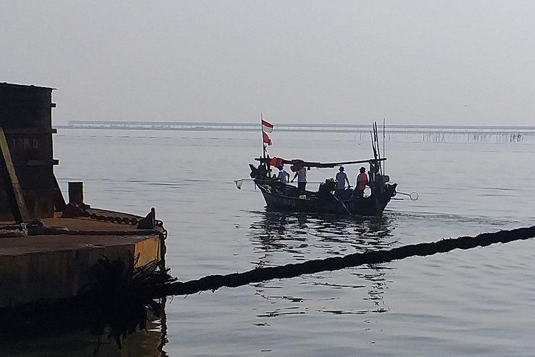 Perahu yang ditumpangi sejumlah nelayan membersihkan sampah yang berada di perairan dekat Pelabuhan KCN Marunda, Jakarta Utara, Kamis (12/9/2019).