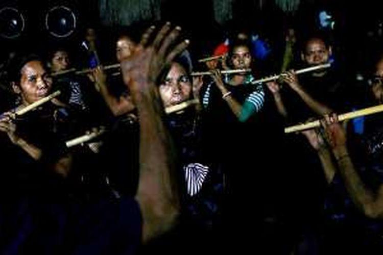 Kaum perempuan Kampung Bena, Kabupaten Ngada, memainkan musik suling saat menyambut tamu, Minggu (14/8/2016).