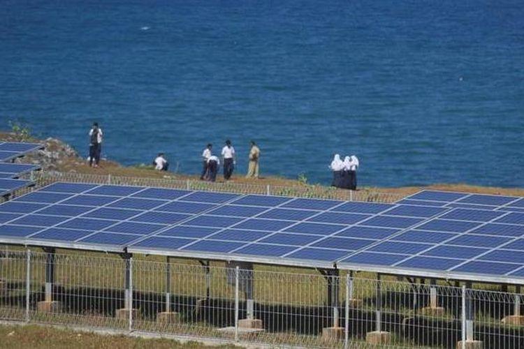 Pelajar berdiri di dekat panel surya yang digunakan untuk membangkitkan tenaga listrik di Baron Technopark, kawasan Pantai Baron, Gunung Kidul, Yogyakarta, Selasa (5/6/2012).