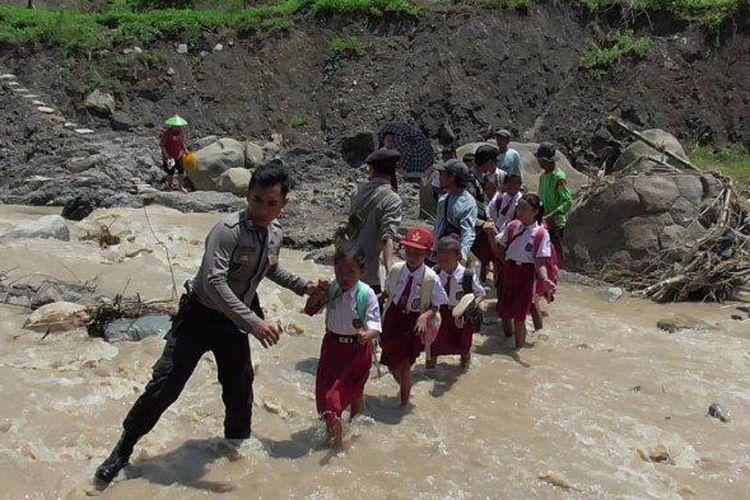 Petugas Polsek Jatigede dan Koramil Jatigede membantu para pelajar menyeberangi Sungai Cisaar. Mereka harus turun ke dasar sungai karena jembatan gantung ambruk