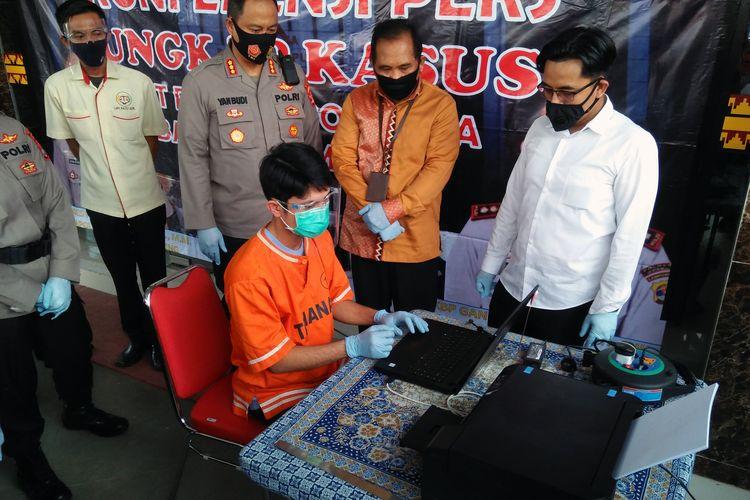 M Javad (27) memeragakan cara dia mencetak uang palsu, Senin (24/8/2020) di Mapolresta Bandar Lampung. Tersangka menggunakan uang palsu untuk membeli barang yang dijual secara online.