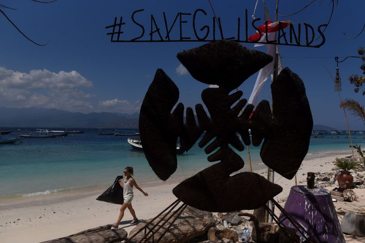 Seorang WNA memungut sampah plastik yang berhamburan di pinggir pantai di Gili Trawangan, Lombok Utara, NTB, Kamis (9/8/2018). Kondisi pulau wisata tersebut sepi pascagempa yang terjadi pada 5 Agustus lalu,  meski sejumlah WNA dan warga lokal masih bertahan di pulau itu.