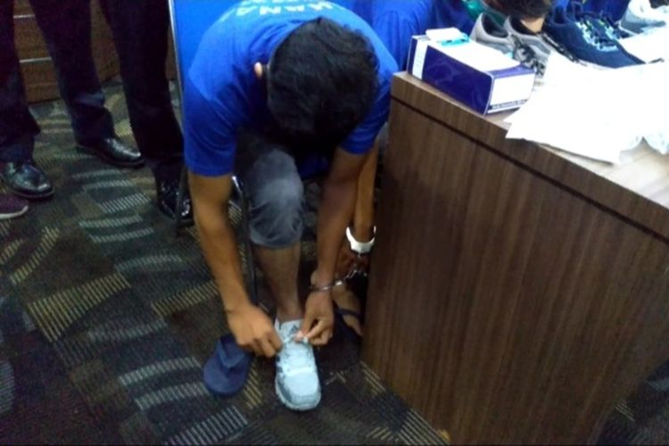 Salah seorang tersangka memperagakan mengenakan sepatu yang di dalamnya berisi sabu. Dia dan 3 temannya ditangkap di Bandara Internasional Kualanamu pada Jumat (22/1/2021) sore saat hendak terbang ke Solo dengan membawa 2 kg sabu.