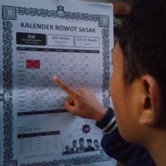 Seorang warga di Mataram menunjukkan kalender Riwot Sasak yang merupakan terjemahan dari papan Warige atau penanggalan tradisional suku Sasak.