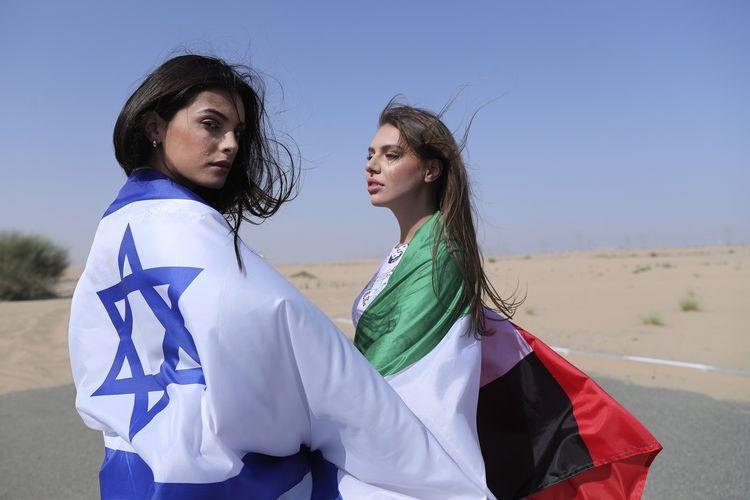 Model Israel May Tager (kiri) yang berbalut bendera Israel, bersama Anastasia Bandarenka model asal Dubai yang mengenakan bendera UEA, saat sesi foto di Dubai pada Minggu (8/9/2020), untuk menandai normalisasi hubungan kedua negara.
