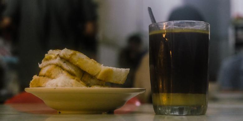 Sepiring roti panggang bersisipkan butter dan segelas kopi butter dari kopitiam Heap Seng Leong.