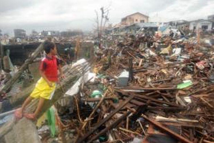 Seorang bocah melihat puing-puing reruntuhan daerah tempat tinggalnya akibat badai Haiyan yang menerjang wilayah Filipina pada Jumat (8/11/2013).