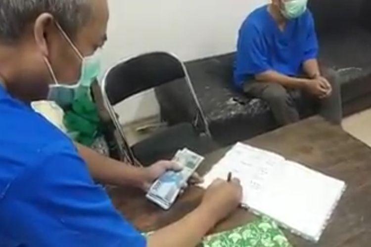 Tangkapan layar video perdebatan antara keluarga pasien dengan petugas di RSUD dr Wahidin Sudirohusodo, Kota Mojokerto, Jawa Timur, terkait permintaan biaya Rp. 3.000.000 untuk pemulasaraan jenazah Pasien Dalam Pengawasn (PDP).