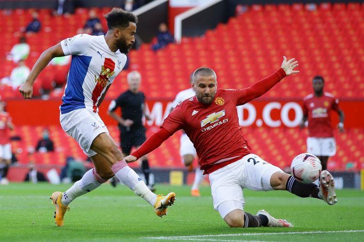 Andros Townsend (kiri) berduel dengan Luke Shaw (kanan) pada laga Man United vs Crystal Palace di Stadion Old Trafford dalam lanjutan pekan kedua Liga Inggris, Sabtu (19/9/2020).