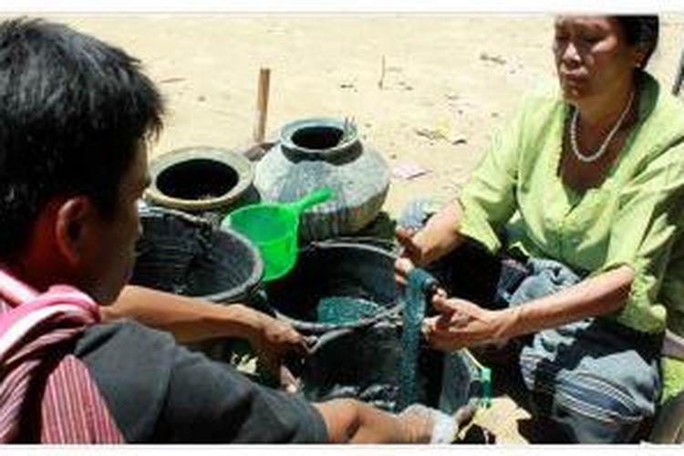 Maroker Siregar, petenun ulos di Desa Huta Nagodang, Kecamatan Muara, Kabupaten Tapanuli Utara, Sumatera Utara, Minggu (22/2), mencelupkan benang hasil pintal ke dalam cairan pewarna alami yang terbuat dari daun salaon. Kerajinan ulos dari benang dengan pewarna alami sudah jarang digunakan seiring maraknya pewarna kimia yang memungkinkan pembuatan ulos lebih cepat dan praktis.