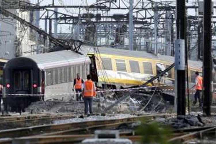 Petugas sedang melakukan evakuasi kecelakaan kereta di stasiun kecil, 20 kilometer di selatan Paris, Perancis, Jumat (12/7/2013) petang waktu setempat. Setidaknya tujuh orang dipastikan tewas seketika, dan jumlah korban kemungkinan bertambah, dari insiden anjloknya kereta antarkota itu. AFP/KENZO TRIBOUILLARD