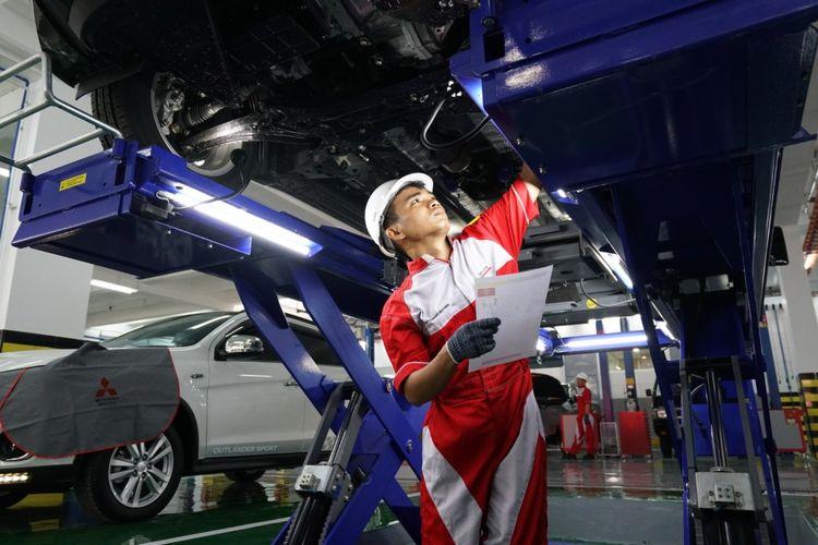 Ilustrasi mekanik mengecek mobil di bengkel mitsubishi