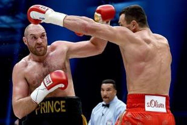 Tyson Fury (kiri) rebut juara dunia kelas berat dari Wladimir Klitschko lewat pertarungan ketat di Duesseldorf, Sabtu (28/11/2015).