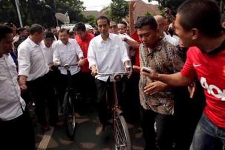 Joko Widodo dan Jusuf Kalla bersepeda menuju Komisi Pemilihan Umum dari kediaman Megawati Soekarnoputri di Teuku Umar, Jakarta, untuk mendaftar menjadi pasangan capres dan cawapres dari PDIP, 19 Mei 2014.