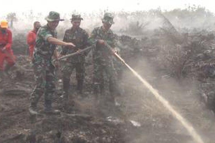 Personel TNI dari Yon Armed 9 Pasopati/Kostrad Jawa Barat mulai bertugas dalam pemadaman kebakaran lahan gambut di Kabupaten Ogan Komering Ilir (OKI), Sumatera Selatan, Sabtu (12/9/2015).