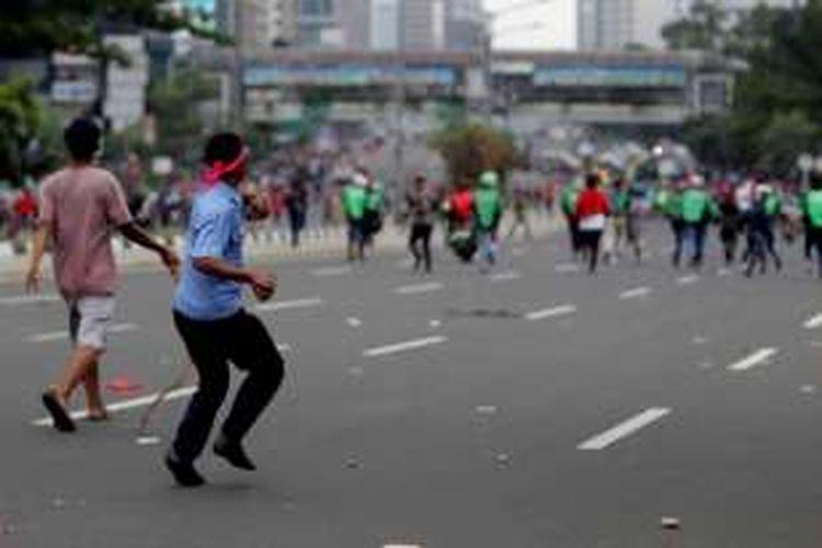 Sejumlah pengemudi ojek online terlibat aksi saling lempar batu dengan para sopir taksi yang berdemonstrasi di Jalan Sudirman, Jakarta, Selasa (22/3/2016). Aksi ini dipicu karena salah satu pengemudi ojek online disweeping oleh para demonstran.