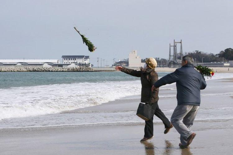 Warga melemparkan karangan bunga untuk menghormati korban tewas dalam bencana tsunami pada 2011 di sebuah pantai, Soma, prefektur Fukushima, Jepang,  pada 11 Maret 2018. (AFP/Jiji Press)