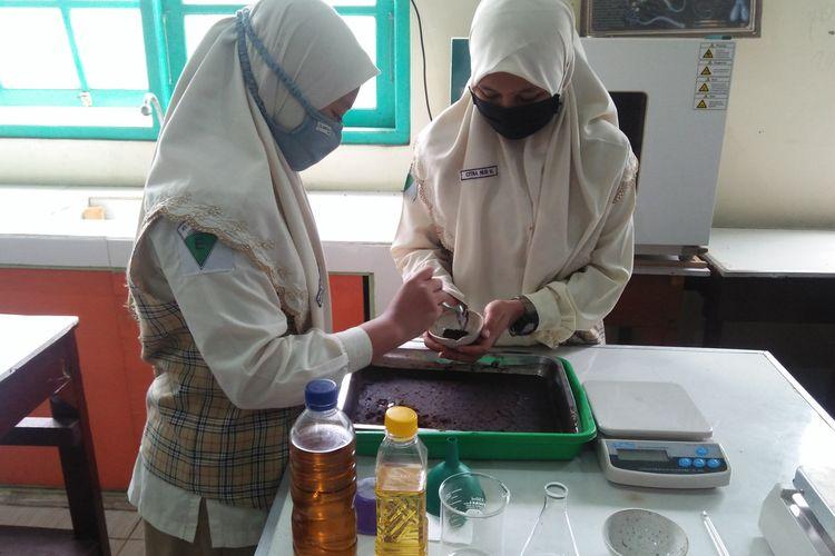Saviola Dinda Rizki Pratiwi dan Citra Nur Marifah, saat menunjukkan pengolahan ampas serbuk kopi sebagai bahan penjernih jelantah, Jumat (27/11/2020).