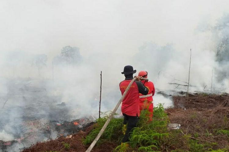 Petugas Manggala Agni Kota Dumai memadamkan titik api karhutla untuk mencegah kabut asap, di Desa Tasik Serai, Kecamatan Talang Mandau, Kabupaten Bengkalis, Riau, Minggu (21/2/2021).
