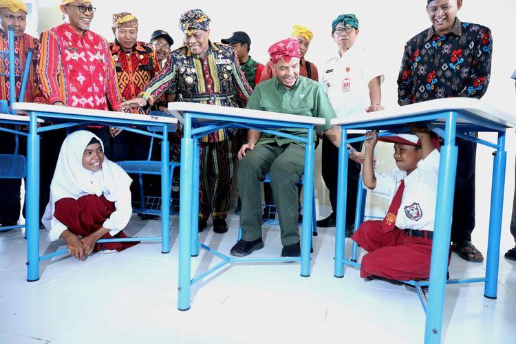 Rika (9) dan Wali (9) siswa kelas 4 SDN 20 Tondo Sirenja Donggala sedang mencoba kursi di kelasnya yang didesain tahan gempa dan berfungsi untuk melindungi diri dari reruntuhan bila terjadi gempa. Mereka mencoba itu disaksikan Gubernur Jawa Tengah Ganjar Pranowo, Rabu(18/9/2019).