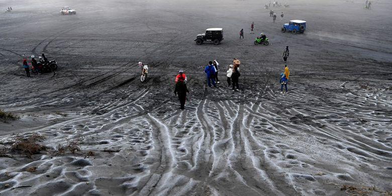 Pengunjung melintas di hamparan pasir yang diselimuti empun upas di kawasan Gunung Bromo, Probolinggo, Jawa Timur, Minggu (30/6/2019). Fenomena embun upas tersebut disebabkan penurunan suhu yang mencapai 0 derajat celcius pada malam hari.