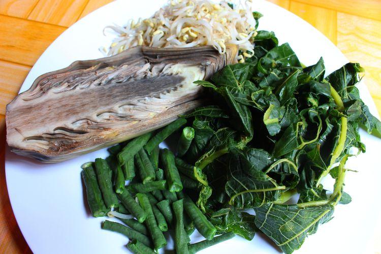 Ilustrasi daun pepaya dan sayur rebus lain.