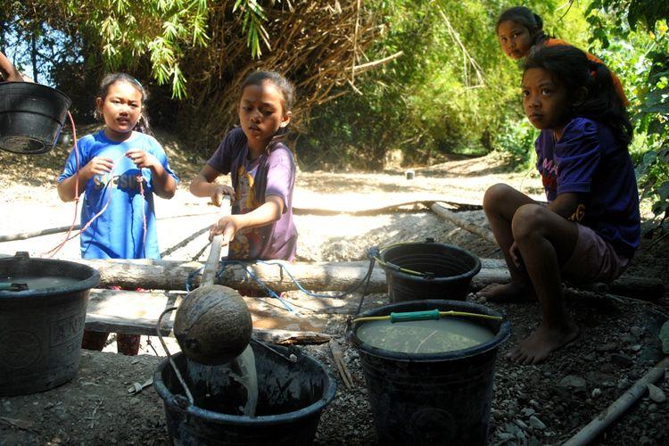Anak-anak Desa Keyongan, Kecamatan Gabus, Kabupaten Grobogan, Jawa Tengah mengambil air keruh untuk kebutuhan sehari-haridari dasar sungai setempat yang sudah mengering, Rabu (26/6/2019) pagi. Tanah tandus yangdigali seukuran tong sampahitu biasa disebut dengan nama belik.