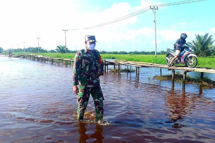 Babinsa Koramil 10/Kunto Darussalam, Koptu Yuliarno memantau warga yang melintas di jalan yang terendam banjir di Desa Sontang, Kecamatan Bonai Darussalam, Kabupaten Rohul, Riau, Sabtu (5/12/2020).