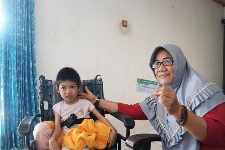 Peserta BPJS Kesehatan Endang Sari Banun bersama cucunya yang mengidap penyakit kelumpuhan otak bersyukur dengan adanya program JKN-KIS, Kamis (20/11/2020).