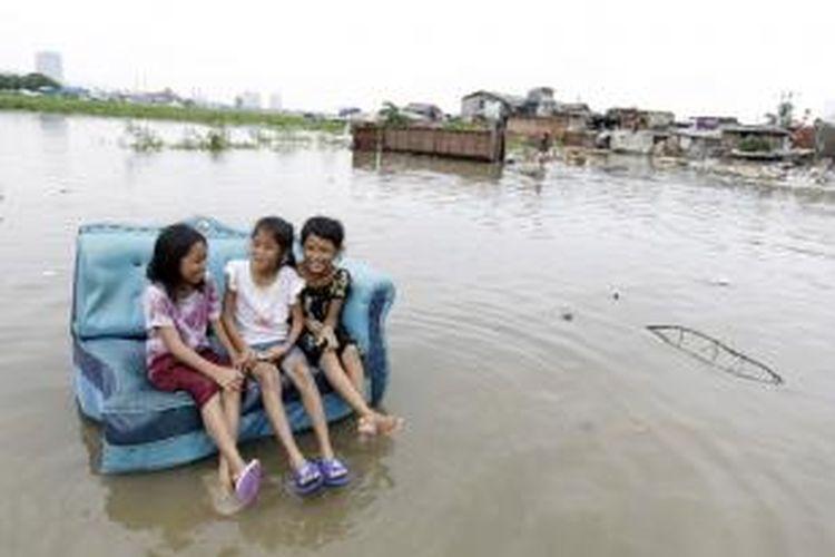 Anak-anak bermain di sekitar banjir yang terjadi akibat meluapnya Waduk Pluit, Jakarta Utara, Minggu (19/1/2014).