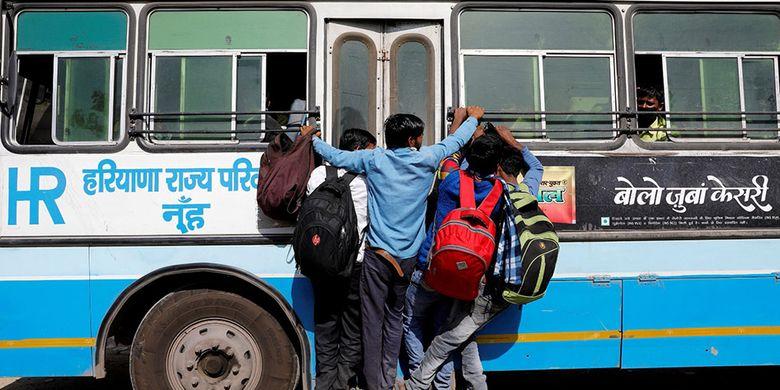 Para pekerja migran bergantungan ke sebuah pintu bus yang bergerak saat mereka kembali ke desa mereka, saat diberlakukan lockdown nasional selama 21 hari untuk membatasi penyebaran penyakit virus corona (COVID-19) di Ghaziabad, pinggiran kota New Delhi, India, Minggu (29/3/2020).
