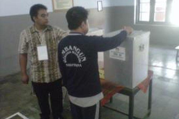 Seorang warga binaan (baju biru) Lapas Kelas II A Kediri, Jawa Timur saat memasukkan surat suara dalam gelaran Pilgub dan Pilwalkot Kediri di TPS khusus Lapas, Kamis (29/8/2013).