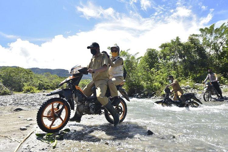 Bupati Luwu Utawa Indah Putri Indriani, saat menyerahkan bantuan PKH dengan mengendarai sepeda motor.