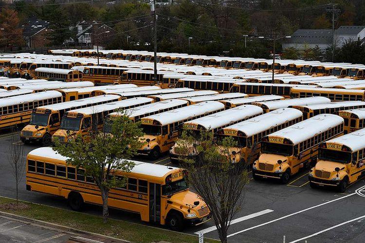 Ratusan bus sekolah terparkir di Depot Bus Kabupaten Arlington, menyusul penutupan sementara kegiatan sekolah terkait wabah virus corona, di Arlington, Virginia, AS, Selasa (31/3/2020). AS kini resmi menjadi epicenter corona di dunia dengan data hingga Selasa (31/3/2020) terdapat 163.429 kasus positif dan korban meninggal 3.148 orang, melebihi Italia, China, dan Spanyol.