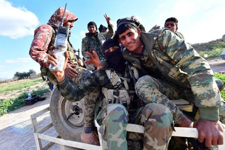 Tentara Pasukan Demokrat Suriah (SDF) mengacungkan jari berbentuk V untuk tanda kemenangan ketika mereka kembali dari garis depan pertempuran melawan ISIS di desa Baghouz, Suriah Deir Ezzor, Suriah, Selasa (19/3/2019). (AFP/CACACE GIUSEPPE)