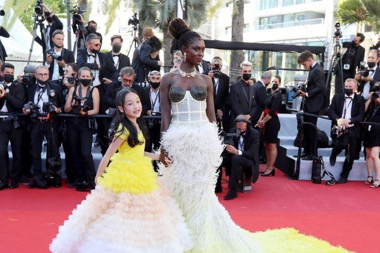 Aktris Inggris Jodie Turner-Smith (kanan) dan aktris cilik keturunan Indonesia Malea Emma Tjandrawidjaja tiba untuk pemutaran perdana film After Yang di Festival Film Cannes, Cannes, 8 Juli 2021.