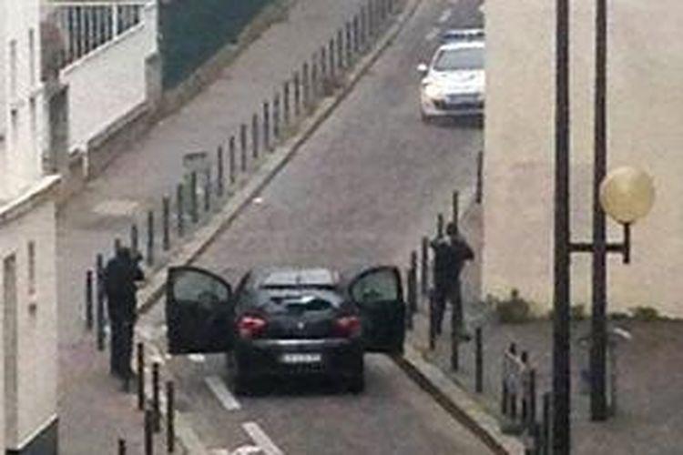 Dua orang bersenjata terlihat berhadapan dengan polisi di dekat kantor majalah satir Charlie Hebdo di Paris, Perancis, Rabu (7/1/2015). Dalam serangan ke kantor majalah itu 12 orang tewas termasuk dua orang polisi.
