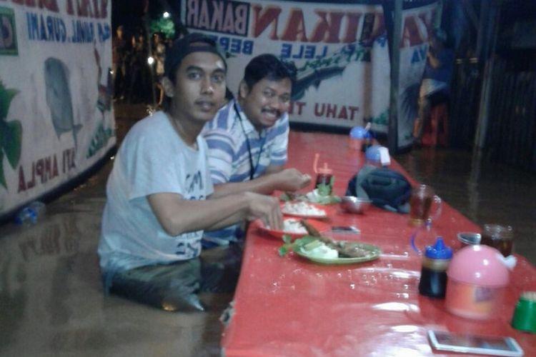 Ahmad Saiful Bahri atau Ipunk makan bersama rekannya di tengah banjir Jakarta.