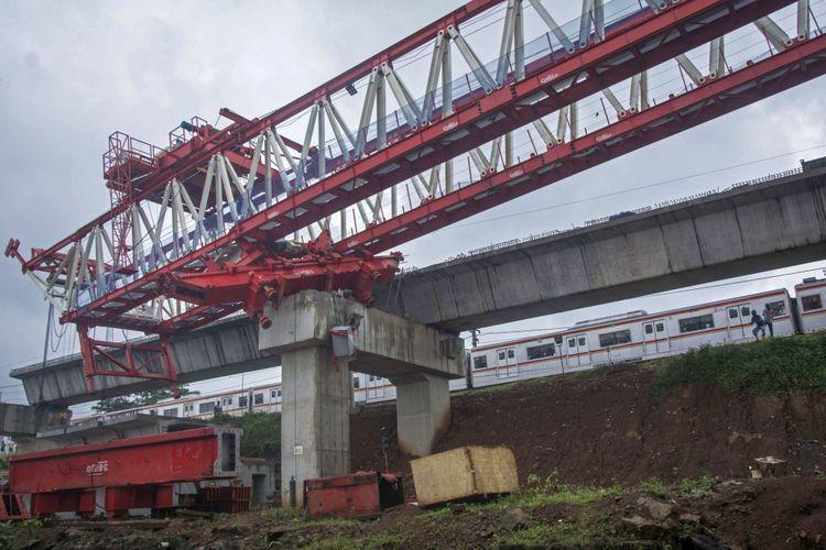 KRL melintas di samping crane proyek pembangunan kontruksi  jalur rel dwi ganda atau double-dobel track (DDT) yang roboh di Jalan Slamet Riyadi, Matraman, Jakarta, Minggu (4/2/2018). Crane dari proyek pembangunan rel Jakarta-Cikarang itu roboh pada Minggu (4/2/2018) sekitar pukul 05.30 WIB dan menyebabkan empat pekerja proyek tersebut tewas.