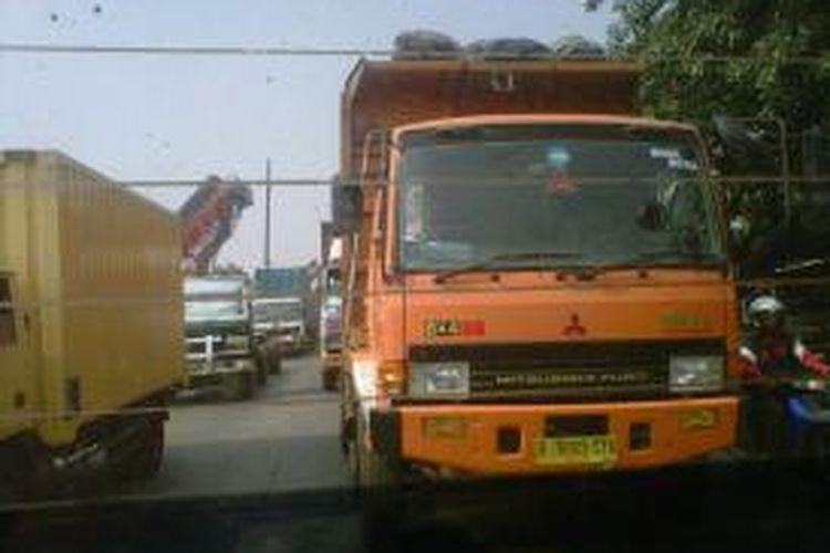 Antrian truk dan kontainer kembali terlihat di sepanjang Jalan Raya Cakung Cilincing, antrian tersebut mengular sampai pos 9 Pelabuhan Tanjung Priok.
