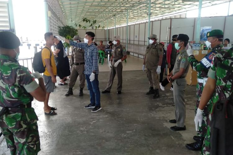 Satgas Pengamanan Perbatasan RI – Malaysia Yonif Raider 600 Modang bersama tim kesehatan Kabupaten Nunukan, Kalimantan Utara, memeriksa suhu tubuh di pintu masuk Pelabuhan Tunon Taka, Selasa (31/3/2020).